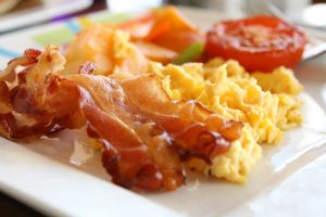 Bacon rashes, scrambled eggs, half a baked tomato on a white serving plate.