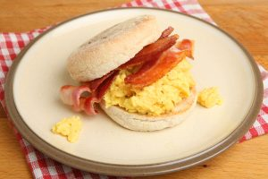 Scrambled egg and bacon in an English muffin served on a dinner plate - Breakfast Catering Menu Melbourne